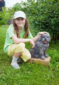 Smiling little girl near to concrete dog — Stock Photo