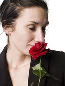 Mujer huele una rosa — Foto de Stock