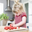 Girl cutting tomatoes — Stockfoto