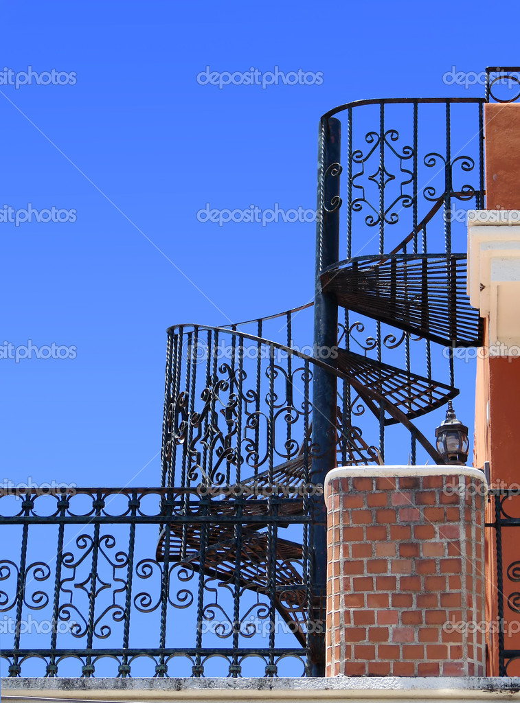 Worm-eye view of an old balcony with wrought iron spiral staircase against bright blue sky                                — Stock Photo #2784479