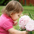Baby girl smelling peony flowers — Stock Photo