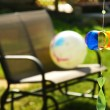 Stock Photo: Pinwheel and loveseat in backyard