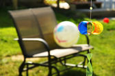 Pinwheel and loveseat in the backyard — Stock Photo