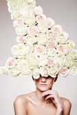Beautiful woman with a rose headwear in a model pose — Stock Photo