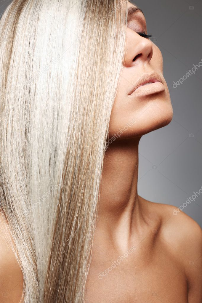Attractive woman with beautiful long blond hair and natural beige make-up on gray background. — Stock Photo #3259907