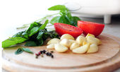 Vegetables on chopping board - focus on tomatoes — Stockfoto