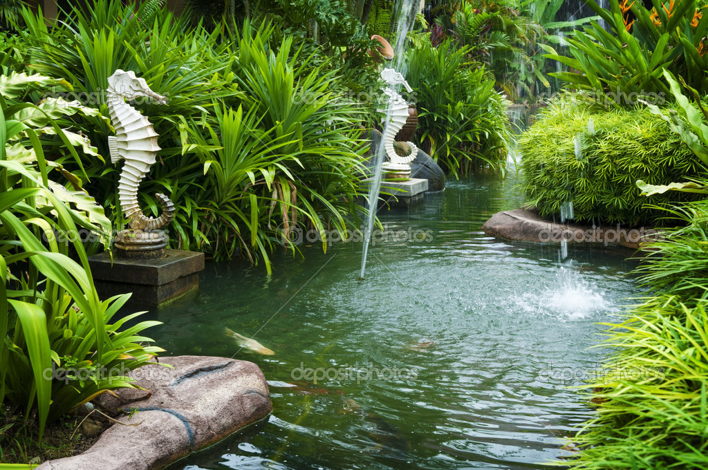 Tropical zen garden view with fountain and green plants.  Stock Photo #3689239