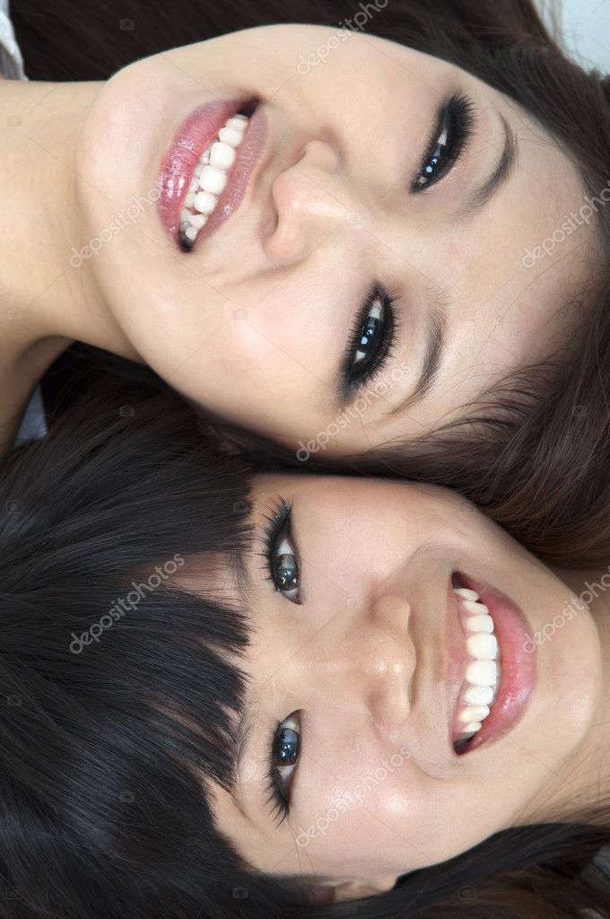 Closeup portrait of happy young girls lying on ground with their heads together  — Stock Photo #3791738