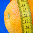 An orange and a measuring tape - Stock Photo
