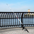 A fishing rod leaned on the fence under — Stock Photo