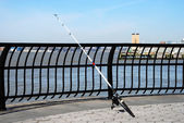 A fishing rod leaned on the fence under — Foto Stock