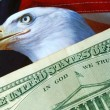 Foto Stock: Dollar bill on AmericEagle flag