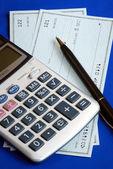 Zkontrolujte a platit účty, tím, že píše šeky, které jsou izolovány na modré — Stock fotografie