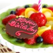 Birthday cake with mixed fruits on top — Stock Photo #3554176