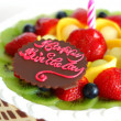 Foto Stock: Birthday cake with mixed fruits on top