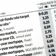 Stock Photo: Check out interest rates from newspaper