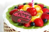Pastel de cumpleaños con frutas mezcladas en la parte superior — Foto de Stock