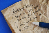 Write some creative business idea on a tissue isolated on blue — Stock Photo