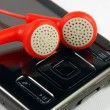 Red earphones on a MP3 player concepts of music download and piracy — ストック写真