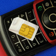Cellular phone with a SIM card isolated on blue — Stock Photo