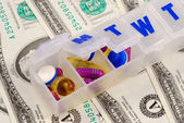 Drug holders on some dollar bills concepts of rising medical cost — Stock Photo