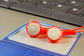 Red earphones on a laptop concepts of music download and piracy — Stock Photo