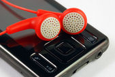 Red earphones on a MP3 player concepts of music download and piracy — Stock Photo