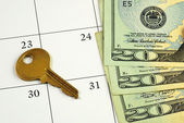 Key and money on a calendar concepts of paying the mortgage on time — Stok fotoğraf
