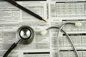 A stethoscope on the top of a medical utilization document — Stock Photo