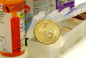 A gold coin on the medicine container concepts of rising medical cost — Stock Photo