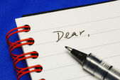 The word Dear with a pen concepts of writing a letter isolated on blue — Stock Photo