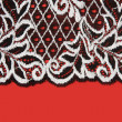 Black lace insulated on red background — Stock fotografie