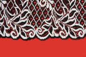 Black lace insulated on red background — Stock Photo