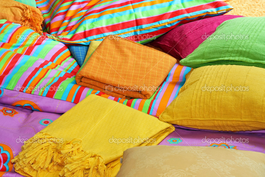 Bunch of pillows and colorful sheets over bed — Stock Photo #3611344