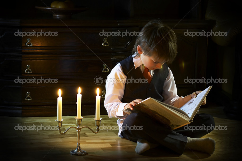 The boy reading the book in the candlelight — Stock Photo #2813837