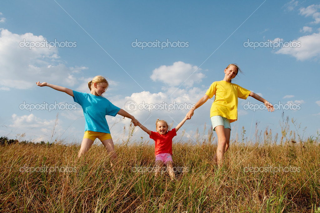Girls wearing colorful t-shirts playing on a meadow — Stock Photo #2855547