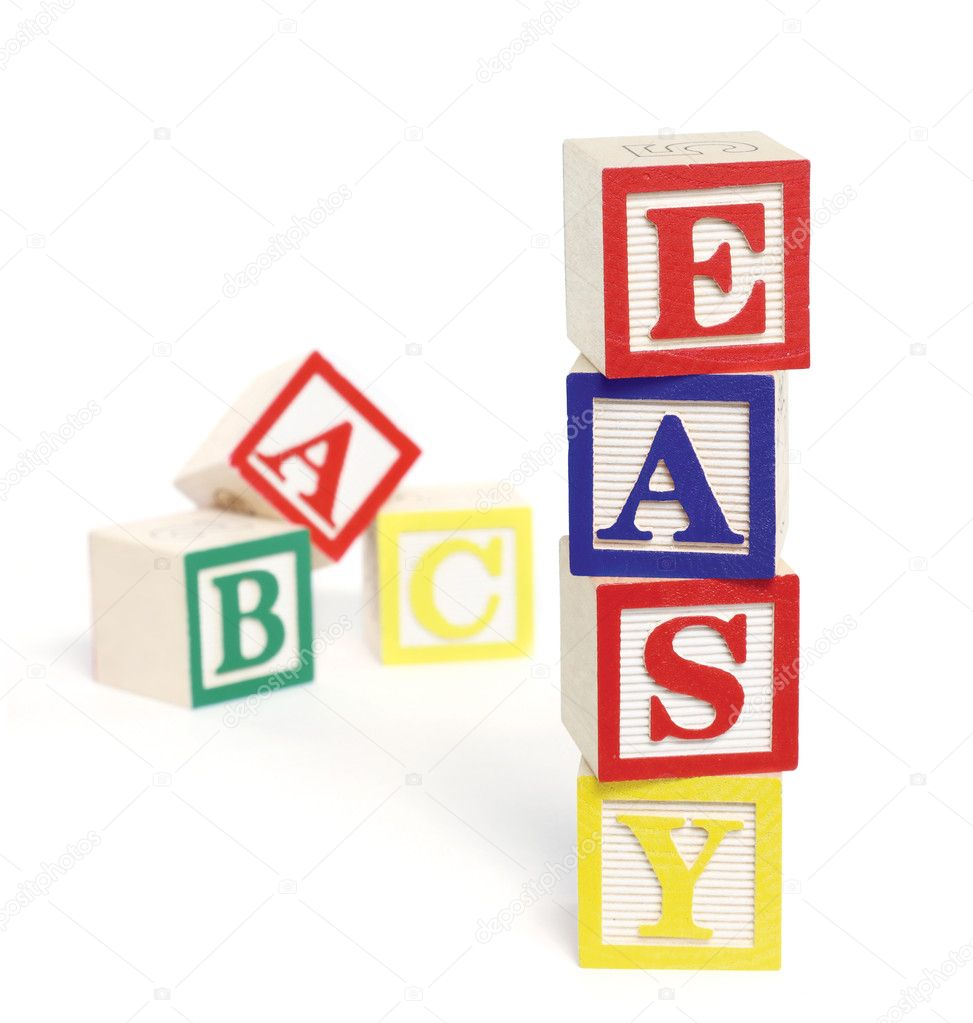 Four wooden alphabet blocks on white background, stacked to form the word, 'easy'. ABC blocks are out of focus in background. Blocks cast shadows.  Stock Photo #3679942