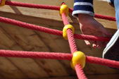 Boy climbing the ropes on playground — Stock Photo