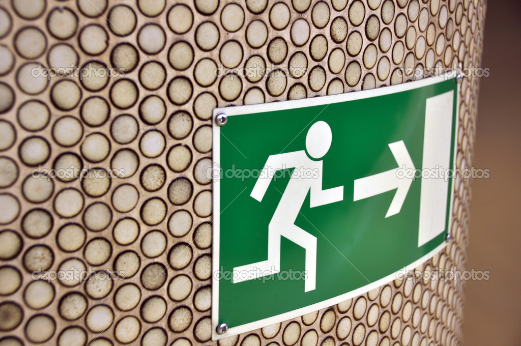 Green emergency exit sign on brown tiled column — Stock Photo #2769980