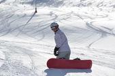 Female snowboarder kneeling — Stock Photo