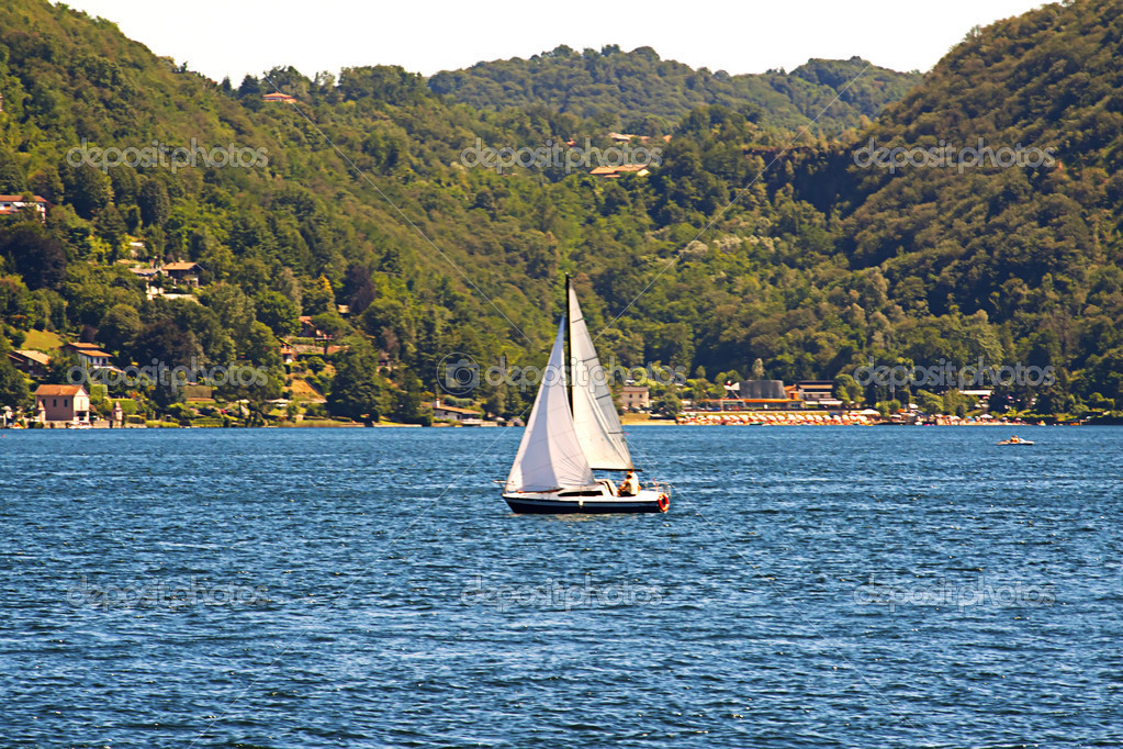 Lonely sail navigating near the border of a lake  Stock Photo #3549331