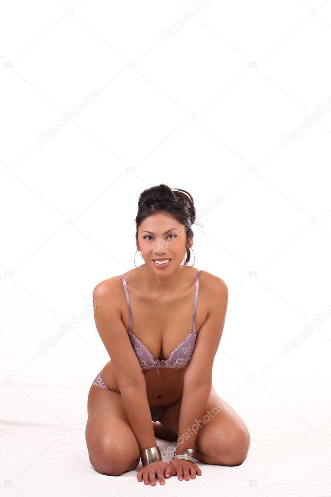 Young woman in bra and panties kneeling on floor