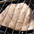 Swordfish steak cooking on barbecue grill closeup — Stock Photo #3476483