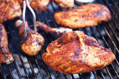 Barbecue chicken cooking on grill with fork — Stock Photo