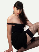 Woman in black dress and fishnet stockings sitting — Stock Photo