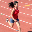 Royalty-Free Stock Photo: Young latina girl running on track shorts red top