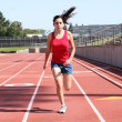 Royalty-Free Stock Photo: Young hispanic teen girl running on track