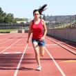 Young hispanic teen girl running on track — Stock Photo #3616476