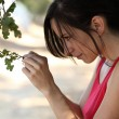Young latina teen girl outdoors ooking at oak leaf — Stock Photo