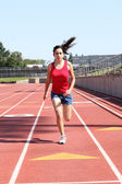 Young hispanic teen girl running on track — Stock Photo